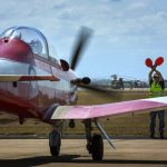 A Royal Australian Air Force PC-9/A aircraft, part of the Roulettes aerobatic display team, is marshalled to a stop after arriving at RAAF Base Townsville for the T150 Defence Force Air Show and Open Day.