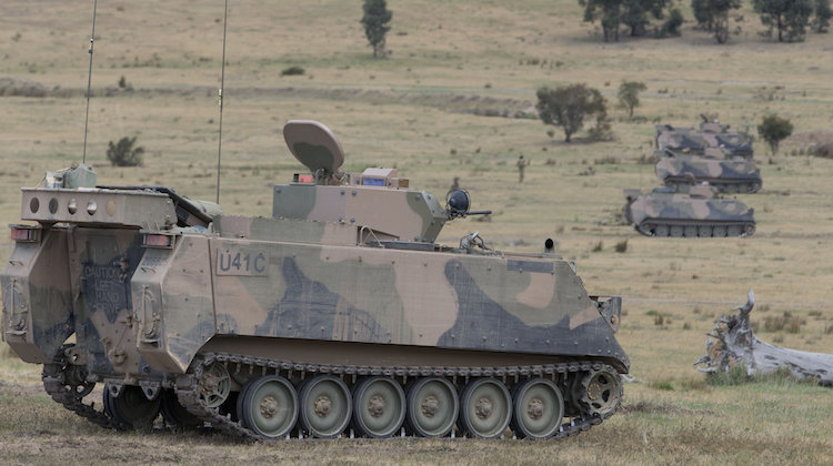 Four Australian Army M113AS4 armoured personnel carriers prepare to engage a target at Puckapunyal training area in northern Victoria during Exercise Chong Ju, a live-fire training exercise by the Combined Arms Training Centre, on 21 October 2015.