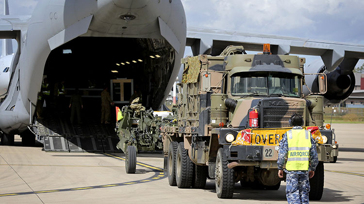 An Australian Army M777 Howitzer is loaded onto a No. 36 Squadron C-17A Globemaster aircraft at Royal Australian Air Force - Amberley.