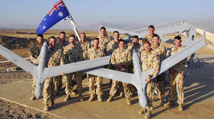 Photo by Corporal Hamish Paterson Caption: Men of the 20th Surveillance and Target Aquisition Regiment proudly display their ScanEagle Unmanned Aerial Vehicles (UAV's) at Camp Holland in Tarin Kowt, Afghanistan. Mid Caption: Mid Caption: The Australian Army's 20th Surveillance and Target Acquisition Regiment has deployed an Unmanned Aerial Vehicle (UAV) detachment to the main Australian operating base in Tarin Kowt, located in Oruzgan Province, Afghanistan. The ScanEagle is a 24-hour capable system that allows the air vehicle's operators to pass real-time information to commanders both in the field and in their headquarters. Powered by a whipper-snipper size engine, the improved muffler system makes the aircraft practically silent at altitude. The UAV's small four-metre wing span and haze-grey paint scheme almost make it invisible, and its high-zoom optics with day and night capability give the air vehicle operators an excellent view of what's happening on the ground as the ScanEagle cruises along for up to 15 hours.