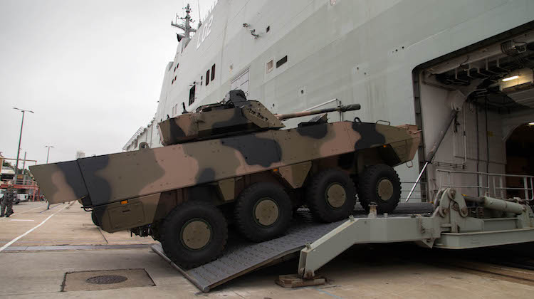 A BAE Systems Australia Patria AMV35 combat reconnaissance vehicle drives onto the heavy vehicle deck of the Royal Australian Navy amphibious ship HMAS Canberra during a series of trials at Fleet Base East in Sydney on 6 December 2016.