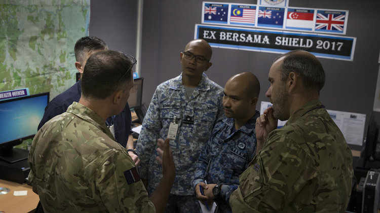 Royal Air Force Wing Commander Colin Would (left) from exercise control inside Headquarters Integrated Area Defence System gives direction to key staff members during Exercise Bersama Shield 17 at RMAF Butterworth, Malaysia.