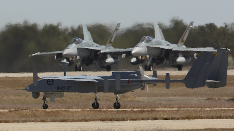 Three Royal Australian Air Force F/A-18 Hornets on the RAAF Base Tindal runway pause for the take-off of the Heron Remotely Piloted Aircraft, all commencing missions during Exercise Diamond Storm 2017.