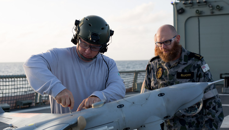 Petty Officer Aircrew Andrew Watson operates ScanEagle on the flight deck of HMAS Newcastle in the Middle East region.