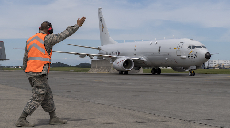 Staff Sgt. Duane Mitchell, 374th Maintenance Squadron transient alert maintenance craftsman, guides a navy P-8A Poseidon aircraft into parking spot, Sept. 15, 2017, at Yokota Air Base, Japan. The Navy P-8A Poseidon came to Yokota as a static display for the Japanese-American Friendship Festival. (U.S. Air Force photo by Airman 1st Class Donald Hudson)