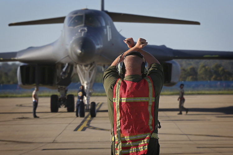 United States Air Force Ground Crew personnel marshall an B-1B Lancer aircraft to RAAF Base Amberley.
