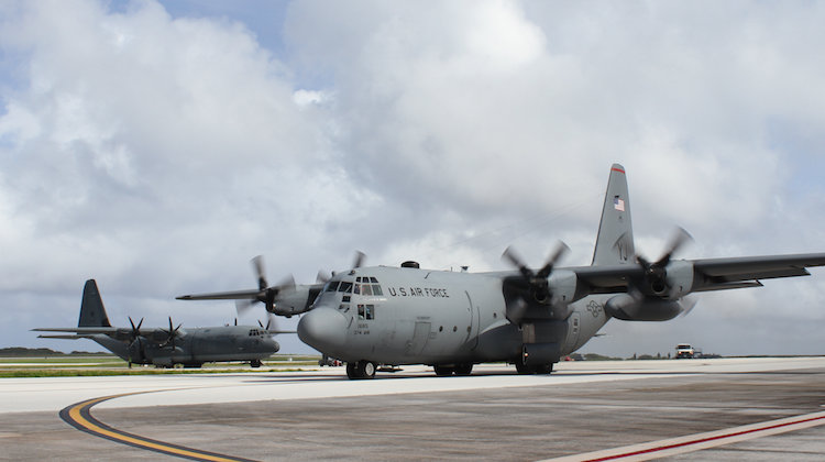 A United States Air Force C-130H Hercules from the 36th Airlift Squadron taxies past a Royal Australian Air Force C-130J Hercules on the flightline at Andersen Air Force Base during Operation Christmas Drop 16.