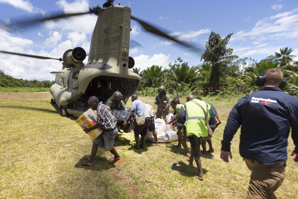 Australian Army aircrew technicians and DFAT employee Jason Moore, assist local people to move aid delivered by a CH-47F Chinook helicopter at a village during Operation PNG Assist 2018. *** Local Caption *** Three Australian Army CH-47F Chinook aircraft, from Townsville based 5th Aviation Regiment, have begun ferrying essential supplies to remote areas of Papua New Guinea affected by a 7.5 magnitude earthquake which struck on 26 February 2018.  Operation PNG Assist 2018 is the ADF contribution to the DFAT-led, Whole of Australian-Government response to the earthquake. The Boeing CH-47F Chinook is the largest helicopter in the Australian Army, and is one of the most versatile.